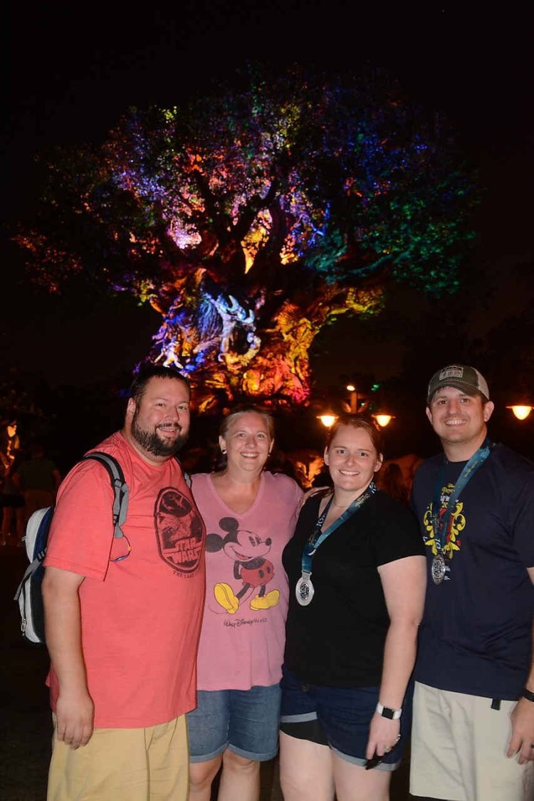family picture in front of Disney tree of life at night