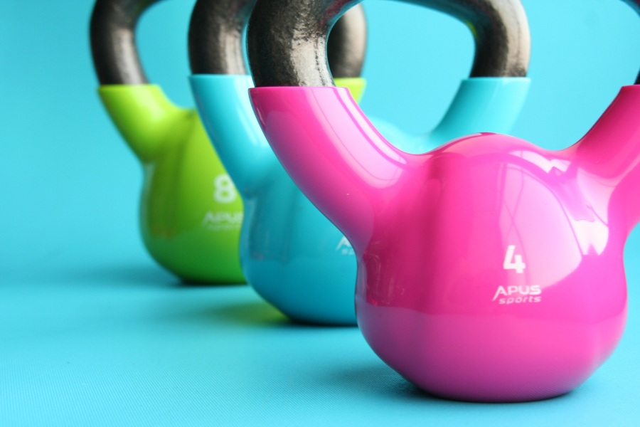 Colorful Kettlebells at Gym, pink, blue, green with blue background.